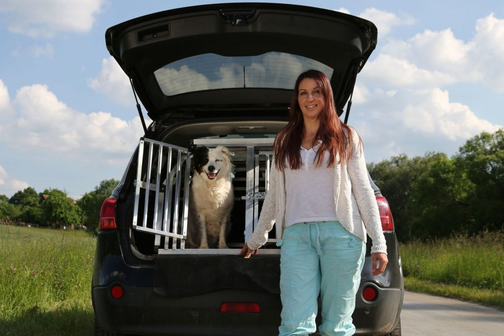 young woman standing and a dog sitting inside a car
